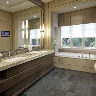 トロントの大きいコンテンポラリースタイルのおしゃれなマスターバスルーム (アンダーカウンター洗面器、ベージュのタイル、アンダーマウント型浴槽、濃色木目調キャビネット、ベージュの壁、スレートの床、御影石の洗面台) の写真