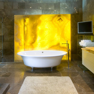 Example of a trendy stone slab claw-foot bathtub design in Other with onyx countertops. Save Photo. bathroom