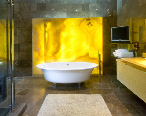 example of a trendy stone slab clawfoot bathtub design in other with onyx countertops
