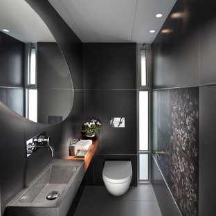 Photo of a contemporary bathroom in Other with a wall mounted toilet, black walls and an integrated sink.