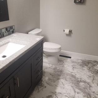 Diseño de cuarto de baño minimalista con armarios estilo shaker, puertas de armario negras, combinación de ducha y bañera, sanitario de dos piezas, paredes grises, encimera de ónix y encimeras grises
