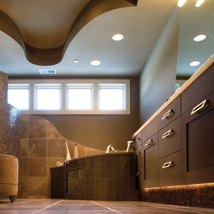 Example of a large trendy master brown tile and ceramic tile ceramic tile corner bathtub design in Minneapolis with flat-panel cabinets, dark wood cabinets, a one-piece toilet, brown walls and a drop-in sink