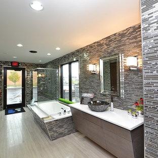Immagine di una grande stanza da bagno padronale industriale con lavabo a bacinella, ante lisce, ante in legno bruno, vasca da incasso, doccia ad angolo, piastrelle grigie, piastrelle a listelli e pareti grigie