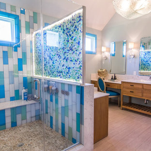 Design ideas for a large beach style master bathroom in Houston with a vessel sink, flat-panel cabinets, light wood cabinets, limestone benchtops, a corner shower, a two-piece toilet, beige tile, glass tile, green walls and light hardwood floors.
