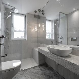 Foto på ett mellanstort funkis badrum, med öppna hyllor, en vägghängd toalettstol, grå väggar, klinkergolv i porslin, ett fristående handfat, kaklad bänkskiva, grått golv och med dusch som är öppen
