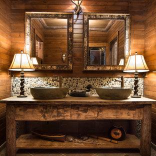Modelo de cuarto de baño rural con lavabo sobreencimera, suelo de baldosas tipo guijarro y suelo de baldosas tipo guijarro