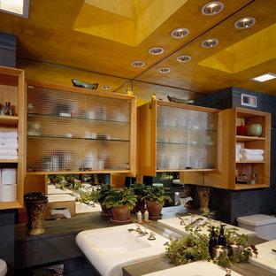 Diseño de cuarto de baño contemporáneo con armarios tipo mueble, puertas de armario de madera clara, sanitario de dos piezas, baldosas y/o azulejos de piedra, suelo de corcho, lavabo encastrado, suelo marrón y ducha con cortina