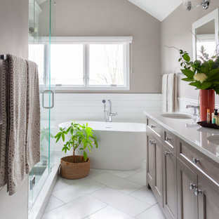 Mid-sized transitional white tile and subway tile white floor, double-sink and vaulted ceiling freestanding bathtub photo in Chicago with shaker cabinets, medium tone wood cabinets, gray walls, an undermount sink, white countertops and a freestanding vanity
