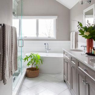 Стильный дизайн: ванная комната среднего размера в стиле современная классика с фасадами в стиле шейкер, фасадами цвета дерева среднего тона, отдельно стоящей ванной, белой плиткой, плиткой кабанчик, серыми стенами, врезной раковиной, белым полом, белой столешницей, тумбой под две раковины, напольной тумбой и сводчатым потолком - последний тренд