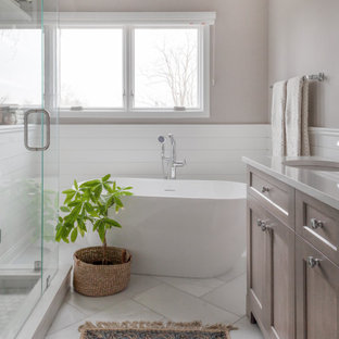 Example of a mid-sized transitional master white tile and marble tile marble floor, white floor, double-sink, vaulted ceiling and shiplap wall bathroom design in Chicago with shaker cabinets, gray cabinets, a two-piece toilet, gray walls, a drop-in sink, quartz countertops, a hinged shower door, white countertops and a freestanding vanity