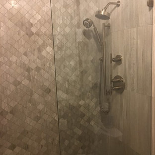 Example of a mid-sized minimalist 3/4 gray tile and limestone tile alcove shower design in Austin with gray walls