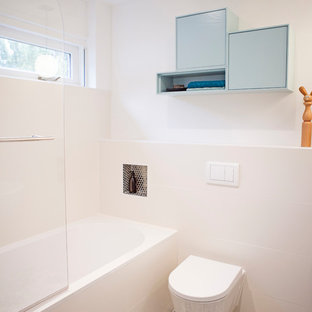 This is an example of a medium sized modern ensuite bathroom in Amsterdam with freestanding cabinets, blue cabinets, an alcove bath, a shower/bath combination, a one-piece toilet, white tiles, ceramic tiles, white walls, terracotta flooring and a wall-mounted sink.