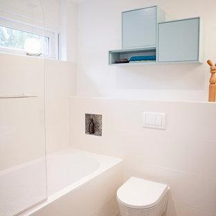 Foto de cuarto de baño principal, moderno, de tamaño medio, con armarios tipo mueble, puertas de armario azules, bañera empotrada, combinación de ducha y bañera, sanitario de una pieza, baldosas y/o azulejos blancos, baldosas y/o azulejos de cerámica, paredes blancas, suelo de baldosas de terracota y lavabo suspendido