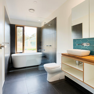Large contemporary 3/4 wet room bathroom in Other with open cabinets, a freestanding tub, a two-piece toilet, gray tile, porcelain tile, beige walls, a vessel sink, wood benchtops, black floor, brown benchtops, a single vanity and a floating vanity.