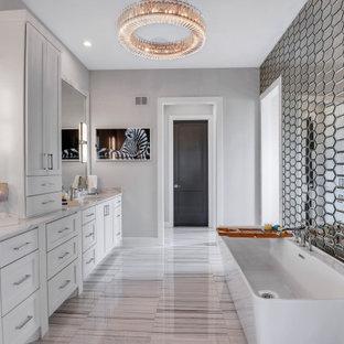 Imagen de cuarto de baño principal, clásico renovado, con armarios estilo shaker, puertas de armario blancas, bañera exenta, baldosas y/o azulejos con efecto espejo, paredes grises, lavabo bajoencimera, encimera de mármol y suelo gris
