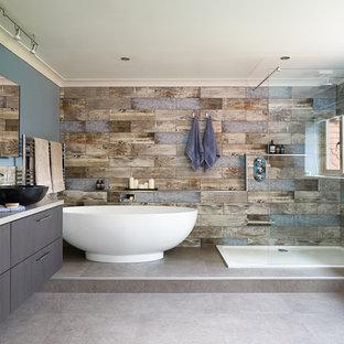 Imagen de cuarto de baño principal, contemporáneo, grande, con puertas de armario de madera en tonos medios, bañera exenta, ducha abierta, sanitario de pared, baldosas y/o azulejos azules, baldosas y/o azulejos de porcelana, paredes azules, suelo vinílico, lavabo sobreencimera, encimera de laminado, suelo gris, ducha abierta y encimeras grises