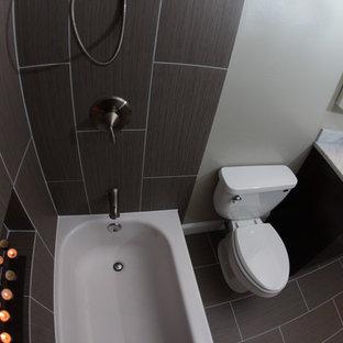 Idéer för ett litet modernt en-suite badrum, med ett undermonterad handfat, släta luckor, skåp i mörkt trä, marmorbänkskiva, en dusch/badkar-kombination, en toalettstol med separat cisternkåpa, grå kakel, porslinskakel, vita väggar och klinkergolv i porslin