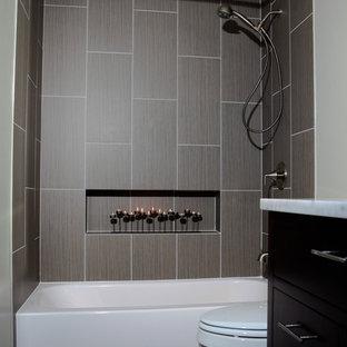 Modern inredning av ett litet en-suite badrum, med släta luckor, skåp i mörkt trä, marmorbänkskiva, en dusch/badkar-kombination, en toalettstol med separat cisternkåpa, grå kakel, porslinskakel, vita väggar och klinkergolv i porslin