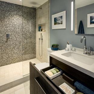 Cette image montre une petit salle de bain principale design avec un placard à porte plane, des portes de placard en bois vieilli, une douche ouverte, un WC à poser, un carrelage multicolore, un carrelage en pâte de verre, un mur bleu, un sol en carrelage de porcelaine, un lavabo encastré, un plan de toilette en quartz, un sol beige et aucune cabine.