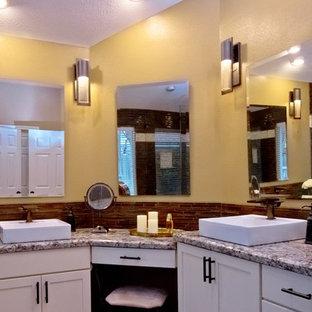 Mittelgroßes Klassisches Badezimmer En Suite mit Schrankfronten im Shaker-Stil, weißen Schränken, Eckbadewanne, Eckdusche, braunen Fliesen, gelber Wandfarbe, Aufsatzwaschbecken, Granit-Waschbecken/Waschtisch, beigem Boden, Falttür-Duschabtrennung, grauer Waschtischplatte und Stäbchenfliesen in Houston