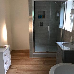 Mittelgroßes Modernes Kinderbad mit verzierten Schränken, weißen Schränken, freistehender Badewanne, offener Dusche, Toilette mit Aufsatzspülkasten, beigefarbenen Fliesen, Terrakottafliesen, beiger Wandfarbe, Laminat, Einbauwaschbecken, Marmor-Waschbecken/Waschtisch, braunem Boden, Falttür-Duschabtrennung und grauer Waschtischplatte in Surrey
