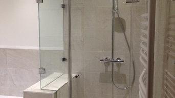 Bathroom installation with bespoke glass shower surround on shelf wall.