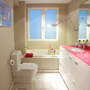 Immagine di una stanza da bagno minimal con lavabo sottopiano, ante lisce, ante bianche, vasca da incasso, WC a due pezzi e top rosa