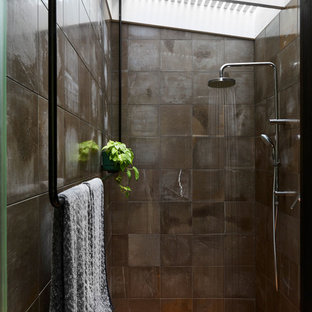Photo of a mid-sized modern bathroom in Brisbane with an open shower, a wall-mount toilet, gray tile, limestone, grey walls, light hardwood floors and an open shower.