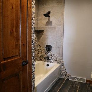 Esempio di una stanza da bagno padronale classica di medie dimensioni con ante in legno scuro, vasca/doccia, piastrelle marroni, piastrelle di ciottoli, pareti grigie, pavimento in gres porcellanato, top in granito e pavimento nero