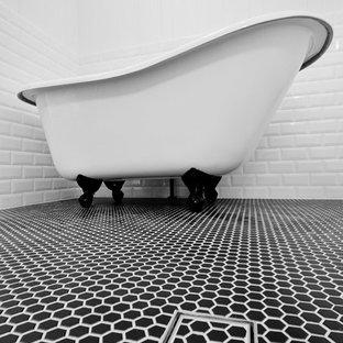 Modelo de cuarto de baño principal, retro, de tamaño medio, con armarios con paneles empotrados, puertas de armario blancas, ducha abierta, baldosas y/o azulejos blancos, baldosas y/o azulejos de cemento, bañera con patas, paredes blancas, suelo de baldosas de cerámica y suelo negro