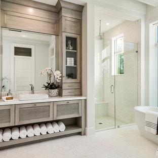Idée de décoration pour une salle de bain tradition avec un placard à porte persienne, des portes de placard grises, une baignoire indépendante, un carrelage beige, un mur blanc, une vasque, un sol beige et une cabine de douche à porte battante.