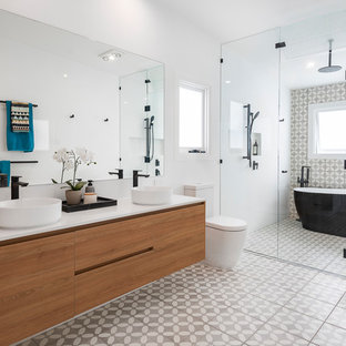 This is an example of an expansive contemporary kids wet room bathroom in Brisbane with a freestanding tub, gray tile, white tile, porcelain tile, grey walls, porcelain floors, a vessel sink, engineered quartz benchtops, grey floor, a hinged shower door, white benchtops, flat-panel cabinets, medium wood cabinets and a two-piece toilet.