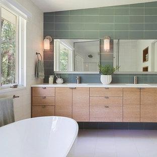 Esempio di una stanza da bagno padronale minimalista di medie dimensioni con lavabo integrato, ante lisce, ante in legno chiaro, vasca freestanding, piastrelle grigie e pareti bianche