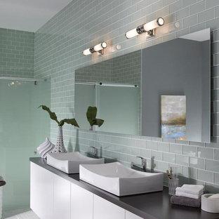 На фото: ванная комната среднего размера в стиле лофт с настольной раковиной, плоскими фасадами, белыми фасадами, столешницей из гранита, отдельно стоящей ванной, унитазом-моноблоком, серой плиткой, плиткой кабанчик, серыми стенами и полом из керамической плитки с