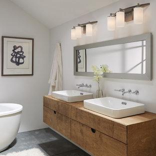 Foto di una piccola stanza da bagno minimal con ante lisce, ante in legno scuro, vasca freestanding, pareti bianche, pavimento in cemento, lavabo rettangolare, top in legno e top marrone