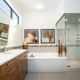 Cette image montre une salle de bain principale vintage de taille moyenne avec un placard à porte plane, une baignoire posée, une douche d'angle, un carrelage gris, un carrelage orange, un carrelage blanc, un carrelage jaune, un mur blanc, un lavabo encastré, des portes de placard en bois brun, un carrelage en pâte de verre, un sol en carrelage de porcelaine, un plan de toilette en quartz, un sol gris et une cabine de douche à porte battante.