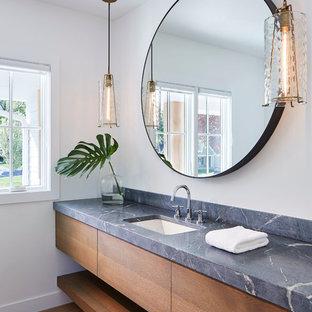 Diseño de cuarto de baño escandinavo, de tamaño medio, con armarios con paneles lisos, puertas de armario de madera oscura, paredes blancas, sanitario de dos piezas, suelo de madera clara, lavabo bajoencimera, encimera de esteatita y suelo beige