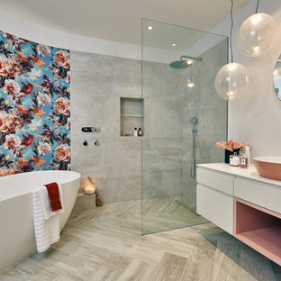 Design ideas for a contemporary wet room in London with flat-panel cabinets, beige cabinets, a freestanding bath, grey tiles, beige walls, a vessel sink, beige floors, an open shower and beige worktops.