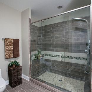 Immagine di una stanza da bagno con doccia design di medie dimensioni con ante di vetro, top piastrellato e piastrelle beige