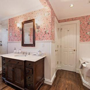 マイアミの大きいトランジショナルスタイルのおしゃれなマスターバスルーム (家具調キャビネット、濃色木目調キャビネット、アルコーブ型シャワー、分離型トイレ、ベージュのタイル、石タイル、ピンクの壁、濃色無垢フローリング、アンダーカウンター洗面器、珪岩の洗面台) の写真