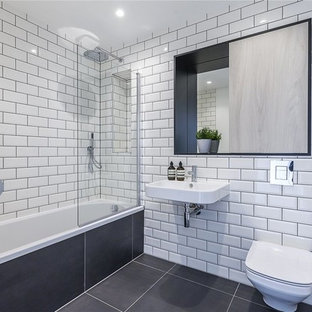 This is an example of a medium sized modern family bathroom in London with recessed-panel cabinets, medium wood cabinets, a built-in bath, a built-in shower, a wall mounted toilet, grey tiles, ceramic tiles, white walls, ceramic flooring, a wall-mounted sink, tiled worktops, grey floors, an open shower and white worktops.