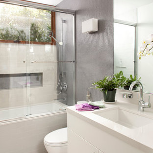 Inspiration for a mid-sized contemporary kids' mosaic tile and gray tile porcelain tile and white floor bathroom remodel in San Francisco with gray walls, flat-panel cabinets, white cabinets, a two-piece toilet, an undermount sink, quartz countertops and white countertops