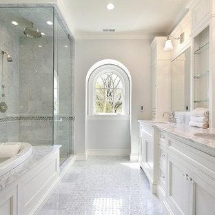 Foto de cuarto de baño principal, clásico renovado, grande, con lavabo bajoencimera, armarios con rebordes decorativos, puertas de armario blancas, encimera de mármol, bañera encastrada, ducha esquinera, sanitario de una pieza, baldosas y/o azulejos amarillos, baldosas y/o azulejos de piedra, paredes grises y suelo de mármol