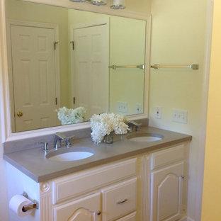 Idee per una piccola stanza da bagno per bambini country con lavabo sottopiano, ante con bugna sagomata, ante bianche, top in cemento, vasca freestanding, WC a due pezzi, piastrelle marroni, piastrelle in terracotta, pareti gialle e pavimento in terracotta