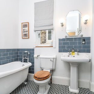 Medium sized classic bathroom in London with a claw-foot bath, a corner shower, a two-piece toilet, blue tiles, metro tiles, white walls, a pedestal sink, multi-coloured floors and a hinged door.