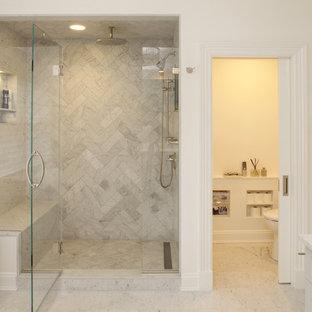 ニューヨークの広いトランジショナルスタイルのおしゃれなマスターバスルーム (シェーカースタイル扉のキャビネット、白いキャビネット、アルコーブ型シャワー、一体型トイレ、グレーのタイル、大理石タイル、白い壁、大理石の床、珪岩の洗面台、白い床、開き戸のシャワー、トイレ室) の写真