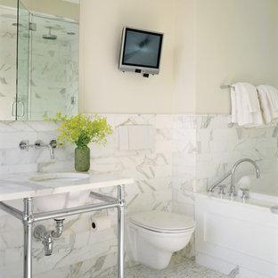 Esempio di una stanza da bagno contemporanea con WC sospeso, lavabo a consolle e piastrelle di marmo