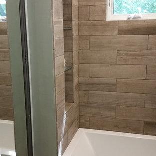 На фото: маленькая главная ванная комната в стиле модернизм с ванной в нише, каменной плиткой, полом из известняка и душем над ванной с