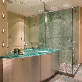 Пример оригинального дизайна: ванная комната в современном стиле с плоскими фасадами, угловым душем, зеленой плиткой, стеклянной плиткой, бежевыми стенами, душевой кабиной, врезной раковиной, стеклянной столешницей и бирюзовой столешницей