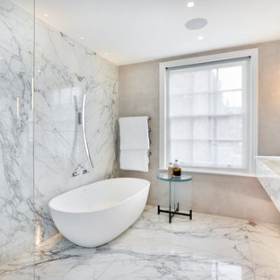 This is an example of a large contemporary ensuite bathroom in London with marble worktops, open cabinets, white cabinets, a freestanding bath, a walk-in shower, grey tiles, beige walls, an integrated sink, grey floors, an open shower and white worktops.
